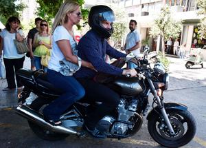 Outgoing Greek Finance minister Yanis Varoufakis leaves onto his motorcycle with his wife Danai after his resignation at the ministry of Finance in downtown Athens on July 6 2015. Varoufakis resigned in what appeared to be a concession by Prime Minister Alexis Tsipras to international creditors after his resounding victory in a historic bailout referendum. AFP/Getty Images