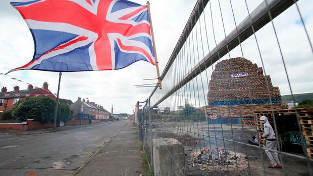 A Union flag flutters in the breeze in front of a bonfire in the village area of Belfast. [Photo: Paul Faith/AFP/Getty Images]