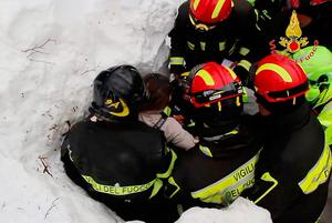 A handout picture released on January 20, 2017 by the Vigili del Fuoco shows a woman (C) being rescued from the Hotel Rigopiano, near the village of Farindola, on the eastern lower slopes of the Gran Sasso mountain, engulfed by a powerful avalanche a day before. AFP PHOTO / VIGILI DEL FUOCO