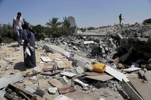 A Palestinian inspects a destroyed house in the Bureij refugee camp in the central Gaza Strip on Friday, Aug. 1, 2014. (AP Photo/Adel Hana)