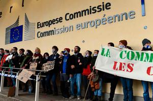People with their mouth muzzled hold banners and placards as they take part in a protest against the EU-Canada Comprehensive Economic and Trade Agreement (CETA) at European Union Commission headquarters in Brussels on October 27, 2016. AFP/Getty Images