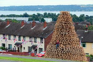 Bonfire builder Ryan Preston poses for a photograph on the Doonbeg bonfire in Rathcoole on July 10, 2017, ahead of the traditional 11th night bonfires. [Photo: Paul Faith/AFP/Getty Images]