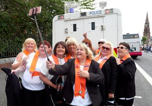 Orangewomen take a selfie photograph beside a police landrover, as the main 12th July parade moves off from Carlisle circus in Belfast, on July 12, 2016. 12th July is the main marching day in the Orange Order calendar. The parades mark the 326th anniversary of King William III's victory at the Battle of the Boyne in 1690. / AFP PHOTO / PAUL FAITHPAUL FAITH/AFP/Getty Images