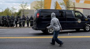 A man watches after throwing an object at police near Mondawmin Mall on April 27, 2015 in Baltimore, Maryland.   Violent street clashes erupted in Baltimore after friends and family gathered for the funeral of Freddie Gray, a 25-year-old black man whose death in custody triggered a fresh wave of protests over US police tactics.  Police said at least seven officers were injured -- one of them was unresponsive -- as youths hurled bricks and bottles and destroyed at least one police vehicle in the vicinity of the shopping mall not far from the church where the funeral took place.  AFP PHOTO / BRENDAN SMIALOWSKIBRENDAN SMIALOWSKI/AFP/Getty Images