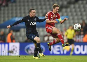 MUNICH, GERMANY - APRIL 09: Philipp Lahm of Bayern Muenchen is challenged by Wayne Rooney of Manchester United during the UEFA Champions League Quarter Final second leg match between FC Bayern Muenchen and Manchester United at Allianz Arena on April 9, 2014 in Munich, Germany.  (Photo by Lars Baron/Bongarts/Getty Images)