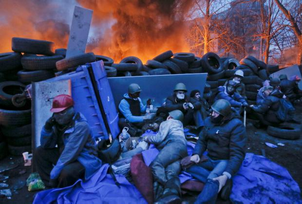 Activists have a rest at the burning barricades, on the side of bloody clashes close to Independence Square, the epicenter of the country's current unrest, Kiev, Ukraine, Thursday, Feb. 20, 2014. Fearing that a call for a truce was a ruse, protesters tossed firebombs and advanced upon police lines Thursday in Ukraine's embattled capital. Government snipers shot back and the almost medieval melee that ensued left scores of people dead. (AP Photo/Efrem Lukatsky)