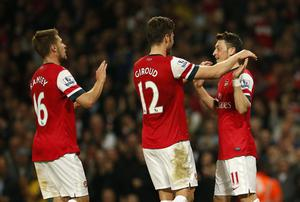 Arsenal's Mesut Ozil (right) celebrates scoring his side's second goal of the game with teammates Olivier Giroud (centre) and Aaron Ramsey (left) during the Barclays Premier League match at the Emirates Stadium