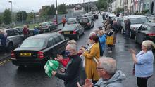 People clap as they watch the funeral cortege of the former SDLP leader John Hume leave St Eugene's Cathedral in Londonderry, following his funeral service.