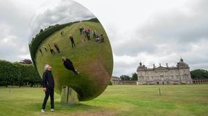 Artist Sir Anish Kapoor looks into his Sky Mirror at Houghton Hall ahead of the opening of an exhibition of his sculptures (Joe Giddens/PA)