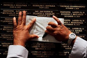 NEW YORK, NY - SEPTEMBER 08:  Family mambers copy the names of loved ones at a ceremony at the Fire Department of New York headquarters where names were added to a memorial wall for deaths related to World Trade Center illnesses on September 8, 2015 in New York City. A total of 21 names were added to the memorial which was unveiled in September 2011 and already lists the names of 89 FDNY members who died of illnesses related to their work at the World Trade Center site during and after the 9/11 attacks.  (Photo by Spencer Platt/Getty Images) *** BESTPIX ***