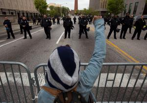 A protester gestures at police during a rally in Baltimore, Maryland, on April 25, 2015, against the death of Freddie Gray while in police custody. Organizers anticipated the biggest outpouring of public anger since Gray, 25, was arrested on April 12, only to die in a coma seven days later from severe spinal injuries.   AFP PHOTO / ANDREW CABALLERO-REYNOLDSAndrew Caballero-Reynolds/AFP/Getty Images
