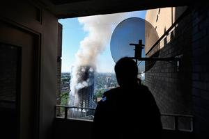 LONDON, ENGLAND - JUNE 14:  A man watches as smoke continues to rise from the building after a huge fire engulfed the 24 story Grenfell Tower in Latimer Road, West London in the early hours of this morning on June 14, 2017 in London, England.  The Mayor of London, Sadiq Khan, has declared the fire a major incident as more than 200 firefighters are still tackling the blaze while at least 30 people are receiving hospital treatment.  (Photo by Leon Neal/Getty Images)
