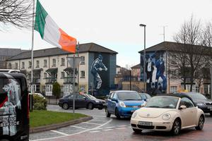 An Irish Flag flys at half mast in the Bogside neighbourhood of Derry on March 21, 2017 as a mark of respect after the death of former Northern Ireland Deputy First Minister Martin McGuinness. AFP/Getty Images