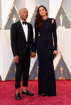 Singer Pharrell Williams and Helen Lasichanh arrive on the red carpet for the 88th Oscars on February 28, 2016 in Hollywood, California. AFP PHOTO / VALERIE MACONVALERIE MACON/AFP/Getty Images