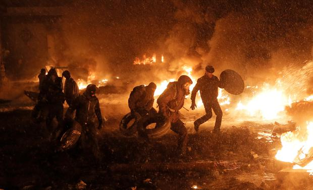 Protesters throw tires in a fire as they clash with police in central Kiev, Ukraine, Wednesday, Jan. 22, 2014. City health officials and police said that two people died of gunshot wounds during the clashes Wednesday morning. But the opposition charges that as many as five people have died. The mass protests in the capital of Kiev erupted after Ukrainian President Viktor Yanukovych spurned a pact with the European Union in favor of close ties with Russia, which offered him a $15 billion bailout. (AP Photo/Efrem Lukatsky)