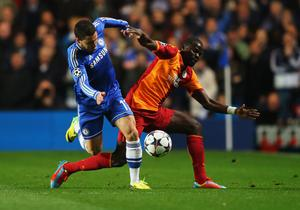 Eden Hazard of Chelsea battles with Emmanuel Eboue of Galatasaray during the UEFA Champions League Round of 16 second leg match between Chelsea and Galatasaray AS at Stamford Bridge on March 18, 2014 in London, England