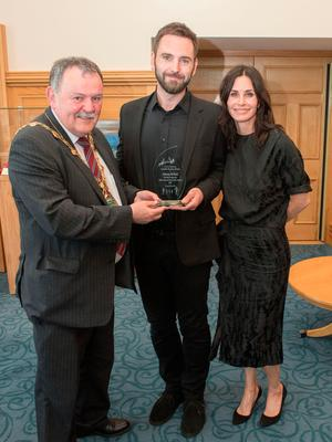 Derry City and Strabane District Council Mayor, Councillor Maolíosa McHugh presents Johnny McDaid, with his fiancée actress Courteney Cox, with an award in recognition of his achievements in the music industry during a reception in the Guildhall