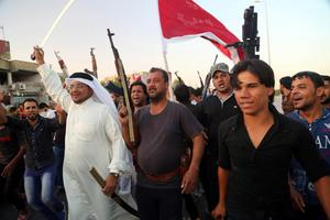 Shiite tribal fighters raise their weapons and chant slogans against the al-Qaida-inspired Islamic State of Iraq and the Levant (ISIL) in Basra, Iraq's second-largest city, 340 miles (550 kilometers) southeast of Baghdad, Iraq, Sunday, June 15, 2014. Emboldened by a call to arms by the top Shiite cleric, Iranian-backed militias have moved quickly to the center of Iraqs political landscape, spearheading what its Shiite majority sees as a fight for survival against Sunni militants who control of large swaths of territory north of Baghdad. (AP Photo/ Nabil Al-Jurani)