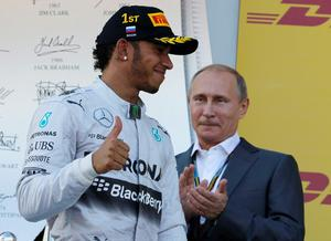 Mercedes driver Lewis Hamilton of Britain gestures on the podium after winning as Russian President Vladimir Putin, right, applauds on the podium during the Formula One Russian Grand Prix at the Sochi Autodrom Formula One circuit, in Sochi, (AP Photo/Luca Bruno)