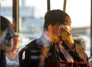 A relative of passengers on flight MH17 wipes his eyes as he waits in a bus to be transported to an unknown location to receive more information, at Schiphol airport in Amsterdam, Thursday, July 17, 2014. Ukraine said a passenger plane carrying 295 people was shot down Thursday as it flew over the country, and both the government and the pro-Russia separatists fighting in the region denied any responsibility for downing the plane. (AP Photo/Phil Nijhuis)