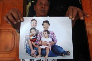 Widi Yuwono, the brother of Yuli Hastini, rear, holds a photograph of his sister's family, showing Hastini, right, her Dutch husband John Paulissen, left, and their two children, Arjun and Sri, who were on Malaysia Airlines Flight 17, Friday, July 18, 2014, at his residence in Solo, Central Java, Indonesia. The Malaysian jetliner that went down in war-torn Ukraine did not make any distress call, Malaysian Prime Minister Najib Razak said Friday, adding that its flight route had been declared safe by the global civil aviation body. (AP Photo)