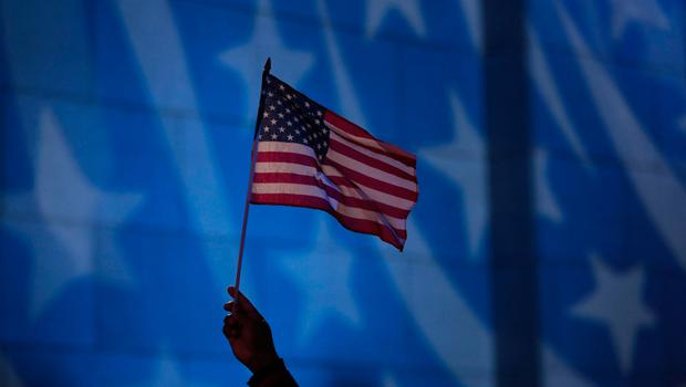 Howard Nizebeth waves a U.S. flag during an Election Day gathering at Rockefeller Center, Tuesday, Nov. 8, 2016, in New York. (AP Photo/Julio Cortez)
