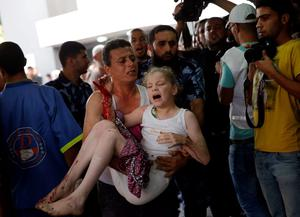 A Palestinian man carries a wounded girl in the emergency room of Shifa hospital in Gaza City, northern Gaza Strip, Sunday, July 20, 2014. (AP Photo/Lefteris Pitarakis)