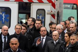 French President Francois Hollande, center, flanked with security forces gestures, as he arrives outside the French satirical newspaper Charlie Hebdo's office, in Paris, Wednesday, Jan. 7, 2015. Masked gunmen stormed the offices of a French satirical newspaper Wednesday, killing at least 11 people before escaping, police and a witness said. The weekly has previously drawn condemnation from Muslims. (AP Photo/Remy De La Mauviniere)