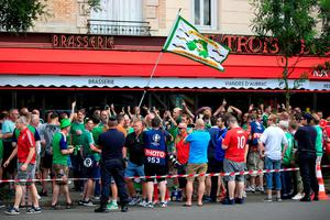 Northern Ireland fans wave a flag outside a bar prior to the round of 16 match at the Parc de Princes, Paris. Jonathan Brady/PA Wire.