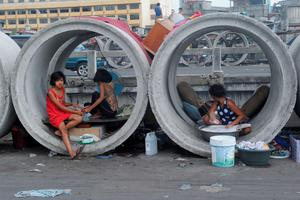 A woman washes laundry as two girls do their nails in culvert sections used as shelters in Manila on April 7, 2015. One in four Filipinos live on less than a dollar a day, according to official data.  AFP/Getty Images