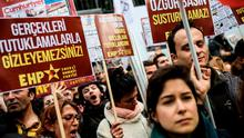 "People shout slogans and hold placards reading ""Free media cannot be silenced, You cannot hide reality by arresting!"" in front of the Cumhuriyet Daily headquarters, on November 27, 2015 in Istanbul, during a demonstration after the arrest of their Editor in Chief. A court in Istanbul charged two journalists from the opposition Cumhuriyet newspaper with spying after they alleged Turkey's secret services had sent arms to Islamist rebels in Syria, Turkish media reported. Editor-in-chief Can Dundar and Erdem Gul, the paper's Ankara bureau chief, are accused of spying and ""divulging state secrets"". Both men were placed in pre-trial detention. AFP PHOTO/OZAN KOSEOZAN KOSE/AFP/Getty Images"