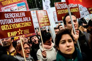 """People shout slogans and hold placards reading """"Free media cannot be silenced, You cannot hide reality by arresting!"""" in front of the Cumhuriyet Daily headquarters, on November 27, 2015 in Istanbul, during a demonstration after the arrest of their Editor in Chief. A court in Istanbul charged two journalists from the opposition Cumhuriyet newspaper with spying after they alleged Turkey's secret services had sent arms to Islamist rebels in Syria, Turkish media reported. Editor-in-chief Can Dundar and Erdem Gul, the paper's Ankara bureau chief, are accused of spying and """"divulging state secrets"""". Both men were placed in pre-trial detention. AFP PHOTO/OZAN KOSEOZAN KOSE/AFP/Getty Images"""