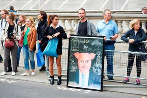 A demonstrator displays a painting depicting former British Prime minister David Cameron in central London on July 13, 2016, on the day new British Prime Minister Theresa May takes over at number 10. Theresa May took office as Britain's second female prime minister on July 13 charged with guiding the UK out of the European Union after a deeply devisive referendum campaign ended with Britain voting to leave and David Cameron resigning. / AFP PHOTO / NIKLAS HALLE'NNIKLAS HALLE'N/AFP/Getty Images