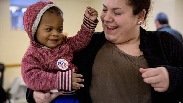 PENACOOK, NH - NOVEMBER 8:  Hayley Bruneau receives a sticker after casting her vote with son Tayvin Faris, 1, at the Immaculate Conception Church on November 8, 2016, in Penacook, New Hampshire. Americans today will choose between Republican presidential candidate Donald Trump and Democratic presidential candidate Hillary Clinton as they go to the polls to vote for the next president of the United States. (Photo by Kayana Szymczak/Getty Images)