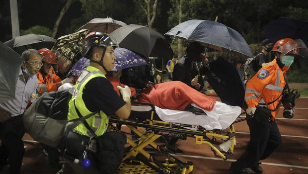 Medical workers move an injured student (Kin Cheung/AP)