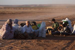 SANLIURFA, TURKEY - OCTOBER 01:  Refugees sit with their belongings after crossing the border from Syria into Turkey on October 1 , 2014 near Suruc, Turkey. Kurdish troops are engaged in a battle against fighters of the Islamic State (IS, also called ISIS and ISIL) to defend the strategic nearby Kurdish border town of Kobani (also called Ayn Al-Arab), which ISIS has surrounded on three sides. The Turkish Parliament is due to vote on a measure on October 2, which would allow Turkish ground forces to enter Syria, creating a buffer zone to protect fleeing refugees from the ISIS advance.  (Photo by Carsten Koall/Getty Images)