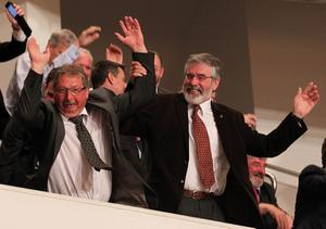 Handout photo issued by Presseye of Finance Minister Sammy Wilson (left) and Gerry Adams TD taking part in an audience wave while waiting  for US President Barack Obama during his visit to the Waterfront Hall, Belfast ahead of the G8 Summit  in County Fermanagh. PRESS ASSOCIATION Photo. Issue date: Monday June 17, 2013. See PA story POLITICS G8. Photo credit should read: Brian Little/Presseye/PA Wire   NOTE TO EDITORS: This handout photo may only be used in for editorial reporting purposes for the contemporaneous illustration of events, things or the people in the image or facts mentioned in the caption. Reuse of the picture may require further permission from the copyright holder.