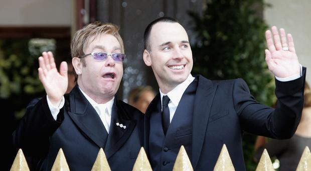 Sir Elton John and David Furnish wave as they leave as a married couple following their civil partnership ceremony at the Guildhall, Windsor on December 21, 2005 in Windsor, Berkshire. (Photo by Chris Jackson/Getty Images)
