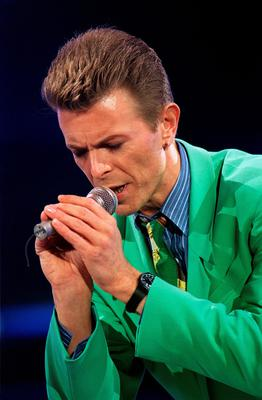 """(FILES) This file photo taken on April 20, 1992 shows British singer David Bowie says a prayer for Freddie Mercury after singing a song in front of the 72,000 people gathered, at Wembley Stadium, in London to attend the Aids benefit concert.  British rock music legend David Bowie has died after a long battle with cancer, his official Twitter and Facebook accounts said on January 11, 2016. Bowie died on Januray 10 surrounded by family according to his social media accounts. The iconic musician had turned 69 only on January 8, which coincided with the release of """"Blackstar"""", his 25th studio album. / AFP / THIERRY SALIOUTHIERRY SALIOU/AFP/Getty Images"""