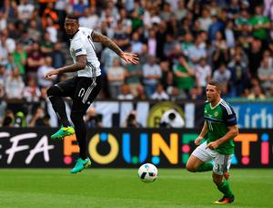 PARIS, FRANCE - JUNE 21: Conor Washington (R) of Northern Ireland and Jerome Boateng (L) of Germany during the UEFA EURO 2016 Group C match between Northern Ireland and Germany at Parc des Princes on June 21, 2016 in Paris, France. (Photo by Charles McQuillan/Getty Images)