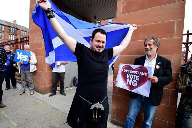 GLASGOW, SCOTLAND - SEPTEMBER 18:  Felipe Perez walks out of polling station at Notre Dame primary school with a Saltire flag, on September 18, 2014 in Glasgow, Scotland. After many months of campaigning the people of Scotland today head to the polls to decide the fate of their country.  The referendum is too close to call but a 'Yes' vote would see the break-up of the United Kingdom and Scotland would stand as an independent country for the first time since the formation of the Union.  (Photo by Jeff J Mitchell/Getty Images)