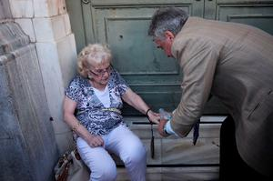 "TOPSHOTS  An elderly woman is assisted by an employee from the National bank of Greece in Athens, after she felt unwell while waiting in line to get her pension, on July 2, 2015.Greece's left-wing government ""may very well"" resign if a referendum this weekend on bailout conditions results in a 'Yes' vote, Finance Minister Yanis Varoufakis said in a radio interview on July 2. AFP PHOTO / LOUISA GOULIAMAKILOUISA GOULIAMAKI/AFP/Getty Images"