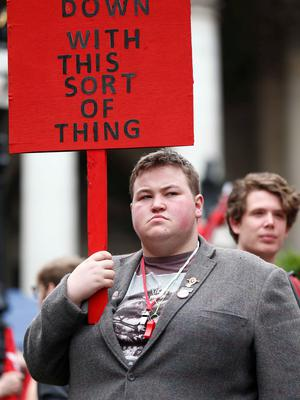 A demonstrator holds a placard as he waits for the start of a protest against the British government's spending cuts and austerity measures in London on June 20, 2015. The national demonstration against austerity was organised by People's Assembly against government spending cuts. AFP/Getty Images