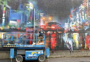 A graffiti artist spray paints a mural on a wall in the cathedral quarter in Belfast during culture night. Picture by Peter Morrison
