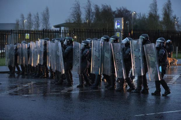 PSNI officers with riot shields line the Springfield road (Liam McBurney/PA)