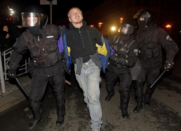 Ukrainian riot police officers detain a protester as they break up a rally at the Independence Square in downtown Kiev, Ukraine, on Saturday, Nov. 30, 2013. The riot police used tear gas when they dispersed the crowd of about 400 protesters who were demanding the resignation of President Viktor Yanukovych, demonstrators said. (AP Photo/Sergei Chuzavkov)