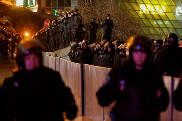 Ukrainian riot police cordon off the Independence Square in downtown Kiev, Ukraine, on Saturday, Nov. 30, 2013. Police in the Ukrainian capital broke up a large anti-government demonstration in the city center before dawn Saturday, swinging truncheons and injuring many. The riot police used tear gas when they dispersed the crowd of about 400 protesters who were demanding the resignation of President Viktor Yanukovych, demonstrators said.  (AP Photo/Sergei Grits)