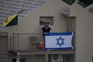 Israeli woman stands on her balcony behind an Israeli flag  overlooking the Gaza Strip on July 20, 2014 in Sderot, Israel.  (Photo by Lior Mizrahi/Getty Images)