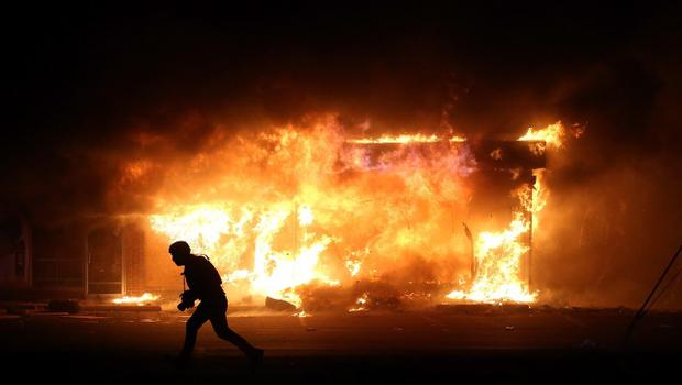 FERGUSON, MO - NOVEMBER 25:  A photographer runs by a burning building during a demonstration on November 25, 2014 in Ferguson, Missouri. Ferguson has been struggling to return to normal after Brown, an 18-year-old black man, was killed by Darren Wilson, a white Ferguson police officer, on August 9. His death has sparked months of sometimes violent protests in Ferguson. A grand jury today declined to indict officer Wilson.  (Photo by Justin Sullivan/Getty Images)