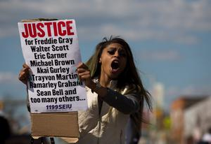 BALTIMORE, MD - APRIL 26:  Baltimore resident Caira Byrd encourages passing cars to honk while she protests in the middle of York Road near Vaughn  Greene Funeral Services during the wake of Freddie Gray, April 26, 2015 in Baltimore, Maryland. Funeral services for Gray, who died last April 16, while in police custody, will be held the morning of April 27, at New Shiloh Baptist Church. (Drew Angerer/Getty Images)